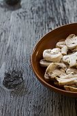stock photo of champignons  - Whole Champignons in a Bowl on Wooden Boards closeup - JPG