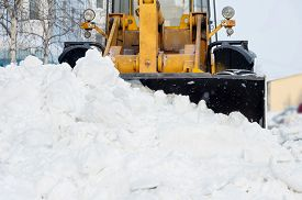 stock photo of bulldozers  - The bulldozer cleans the road after a blizzard - JPG