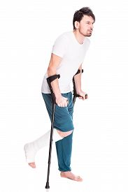 pic of crutch  - Full length view of a young man with broken leg is using crutch isolated on white background - JPG