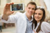 picture of love-making  - Young beautiful couple making selfie in the street - JPG