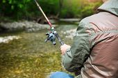 image of fly rod  - Fisherman with fly-fishing on mountain river. Spring time ** Note: Shallow depth of field - JPG