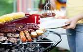 image of grilled sausage  - Closeup of woman dishing out grilled sausage - JPG