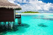 stock photo of pacific islands  - Over water bungalow with steps into amazing blue lagoon with island in distance - JPG