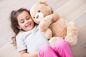 stock photo of teddy  - Girl with teddy bear lying on wooden floor at home - JPG