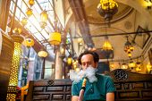 foto of shisha  - Man smoking turkish hookah in the cafe with coloful lamps on background in Istanbul - JPG