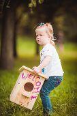 foto of nesting box  - Little girl with bird nesting box in green park  - JPG
