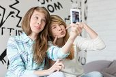 stock photo of pouting  - Cute sisters pouting while taking photos with smart phone at home - JPG