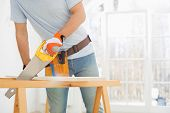 picture of sawing  - Midsection of man sawing wood in new house - JPG