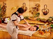 foto of black woman spa  - Young woman with black hair getting massage in bamboo spa - JPG