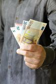 stock photo of holding money  - businessman hands holding european money (euro) - business, people, finances and money concept