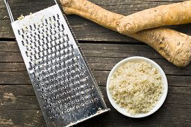 stock photo of grated radish  - grated horseradish root on kitchen table - JPG