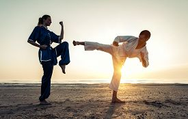 stock photo of karate-do  - couple training in martial arts on the beach at sunrise - JPG