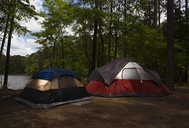 stock photo of nylons  - Two nylon tents at dusk at a campsite next to a lake - JPG