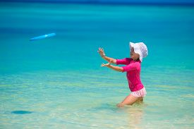 image of frisbee  - Little girl playing frisbee on a tropical white beach - JPG
