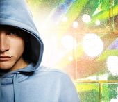 stock photo of break-dance  - Cool looking man in a hood over abstract graffiti background - JPG