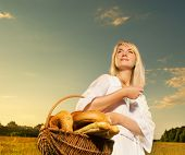pic of household farm  - Beautiful young woman with a basket full of fresh baked bread - JPG