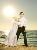 stock photo of ballroom dancing  - Young couple dancing on a beach at sunset - JPG
