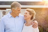 Постер, плакат: Happy senior couple standing out of the house and looking at each other Portrait of smiling senior
