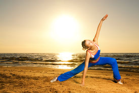 foto of athletic woman  - Beautiful young woman doing fitness exercise on a beach at sunset - JPG