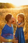 Family Time. Father And Daughter On The Meadow At Sunset. The Little Girl Is Holding Her Father By T poster