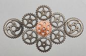 Rose-gold cogwheel and bunch of silver cogwheels on a light grey background. Uniqueness and individu poster