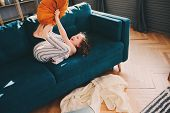 Happy Kid Girl Having Fun At Home In Lazy Weekend Morning, Fighting With Pillows On Cozy Couch In Pa poster