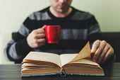 Man In Dark Striped Sweater Sitting By Wooden Table And Reading Book While Holding Mug. Evening Rout poster