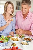 stock photo of portrait middle-aged man  - Mid age couple enjoying meal at home - JPG