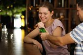 Young drunk couple fighting for bottle of beer in bar. Alcoholism problem