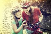 Bikes cycling weekend for girls. Children training rides bicycle in cycling look at compass. People  poster