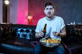Young Supporter Man Watching Football Game On Television Sitting At Home Couch With Ball Beer And Ch poster