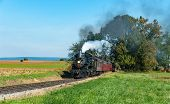 Vintage Steam Locomotive With Vintage Passenger Train Puffing Smoke And Steam On A Summer Day, With  poster