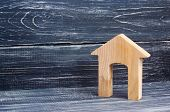 Figurine Of A Wooden House With A Large Doorway On A Background Of Black Boards. Concept Of Real Est poster