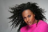 stock photo of female model  - studio portrait of african american woman with blowing hair - JPG