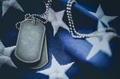 Worn USA military dog tags close up on US American flag with blank space for text poster