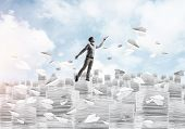 Man In Casual Wear Keeping Hand With Book Up While Standing Among Flying Paper Planes With Cloudly S poster