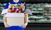 Food Delivery Service For Order Online Grocery Shopping Concept. Delivery Man In Blue Uniform Hand H poster