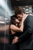 Beautiful Seductive Couple Hugging And Kissing In Lift poster