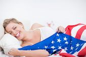 stock photo of american flags  - Laughing blonde woman with a US flag in her bed - JPG