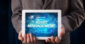 Young business person working on tablet and shows the inscription: ASSET MANAGEMENT, business concep poster