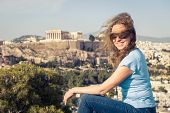 Young Pretty Woman Sits At Hilltop In Athens, Greece. Beautiful Adult Girl Tourist Smiles Overlookin poster