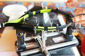 Stringer Pulls Strings On Tennis Racket On Equipment Stringing Machine. poster