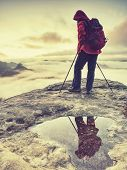 Hiker Woman With Red Backpack And Trekking Sticks Walking At Edge Of Rocky Mountains. Young Hiker Wo poster
