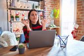 Beautiful woman sitting at the table working with laptop at home around christmas lights relax and s poster