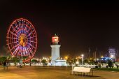 Seafront Promenade In Batumi At Night. Evening Illumination Lights In Ferris Wheel And Old Lighthous poster