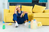 Young Female Worker Of The Cleaning Service Sitting Near The Couch And Feeling Tired After Washing F poster