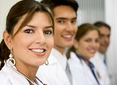 foto of medical doctors  - Beautiful female doctor facing the camera with her team behind her - JPG