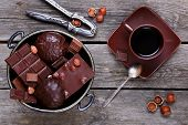image of melchior  - Bowl with chocolate nuts nutcracker and coffee on a gray wooden background - JPG