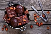 picture of melchior  - Bowl with chocolate nuts and nutcracker on a gray wooden background - JPG
