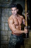 pic of hot pants  - Handsome muscular man shirtless wearing military pants in front of stone wall - JPG